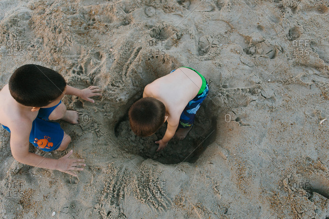 Young boys digging a hole on a sandy beach