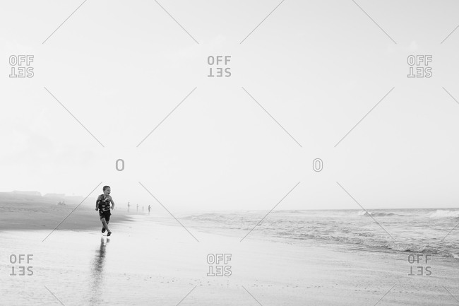 Young boy running on a beach