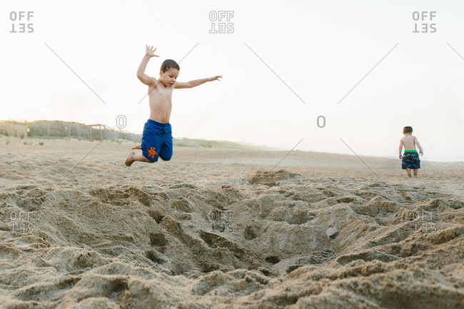 Young boy jumping on a sandy beach