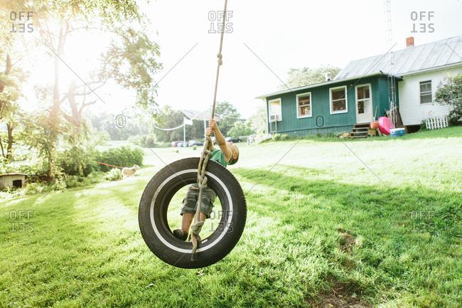 Boy leaning back on tire swing