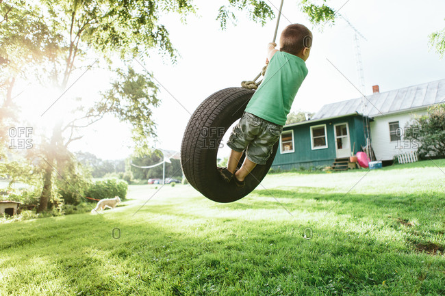 Boy backward on tire swing
