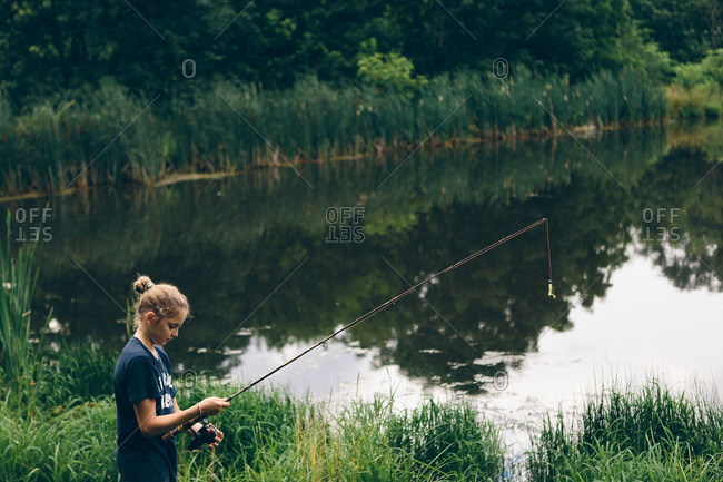 Side view of a girl standing with fishing rod