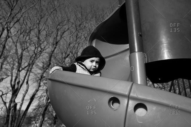 Boy sliding down a spiral slide on playground