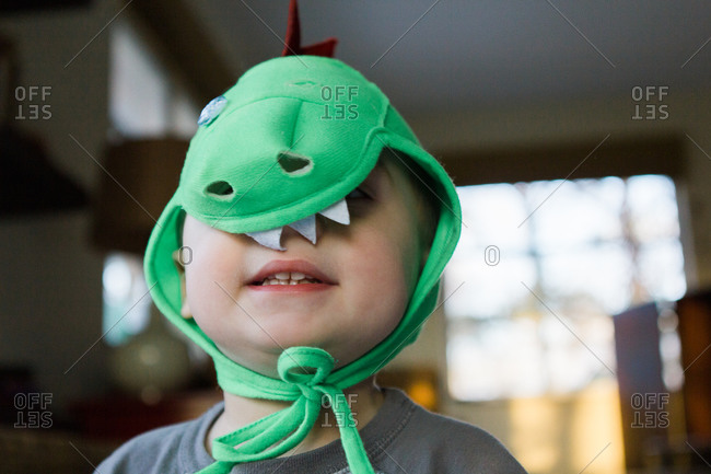 Young boy in dinosaur mask