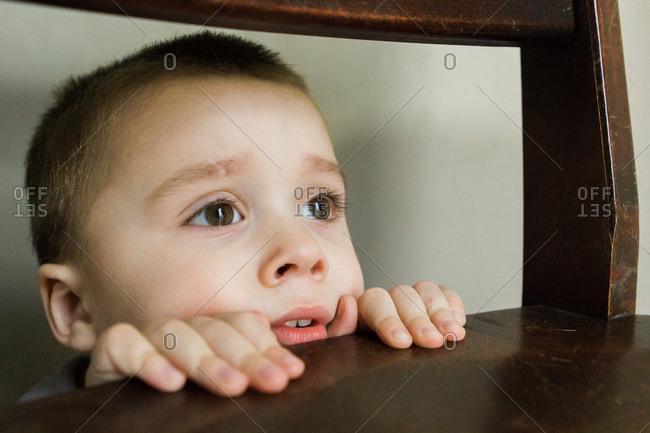 Boy peeking through chair from left