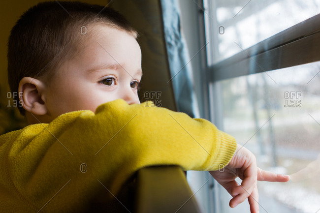 Young boy in yellow sweater looking out window