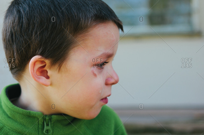 Young boy in green shirt crying