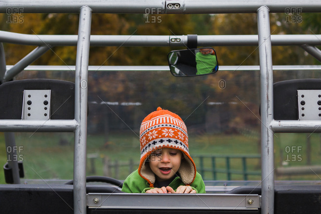 Young boy in orange hat playing at playground