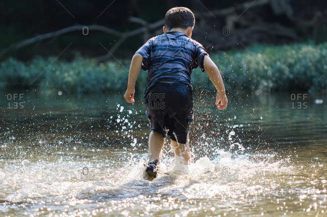 Rear view of boy jumping in water