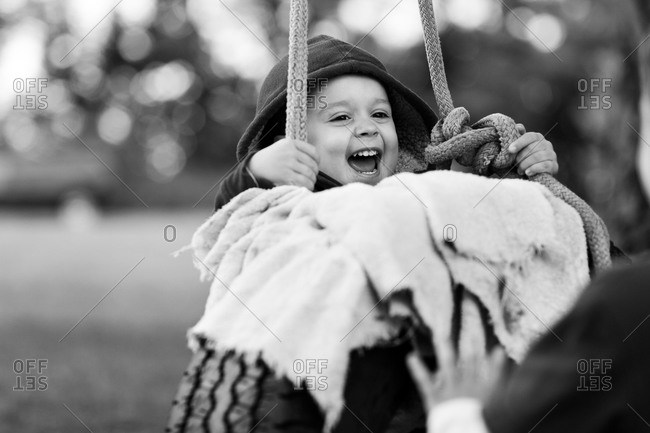 Boy laughing on tire swing