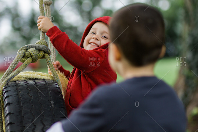 Boy being pushed on tire swing