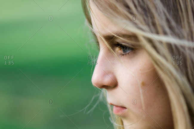 Profile of a blonde girl on a meadow
