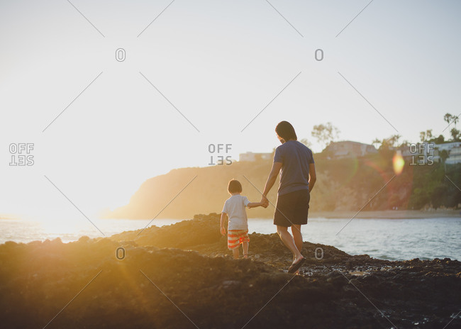 Father and son, hand-in-hand, walking along a rocky shore