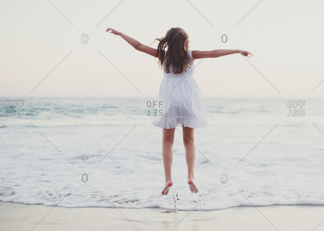 Young girl leaping on the beach