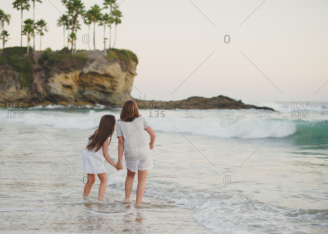 Sisters wading in the surf