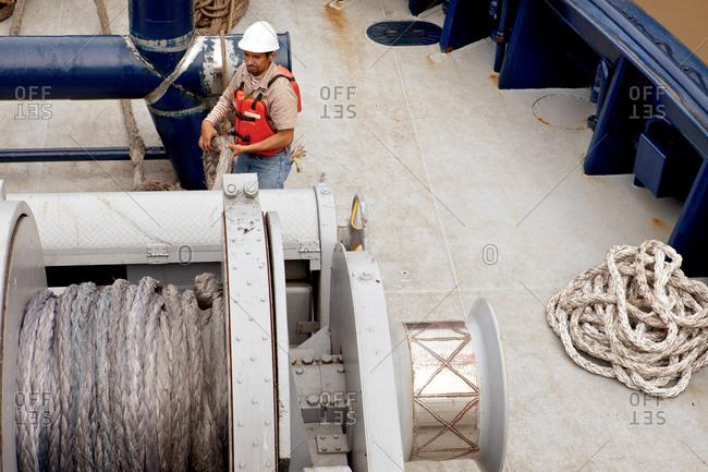 Crew member of  tugboat preparing winch