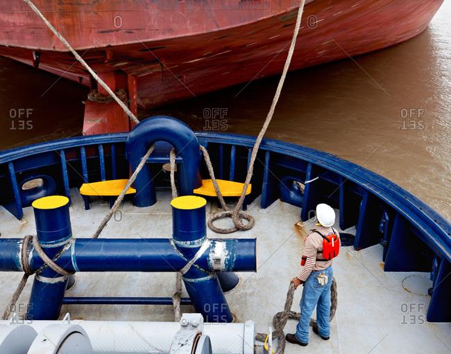 Tugboat crew member arranging ropes