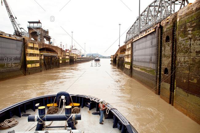 Tugboat and crew passing through Miraflores Locks