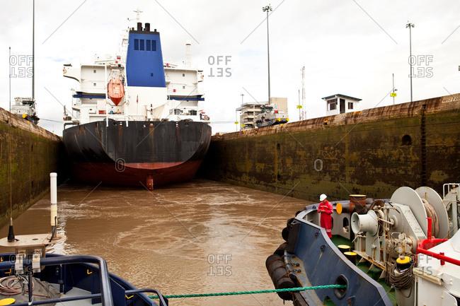 Two tugboats following cargo ship