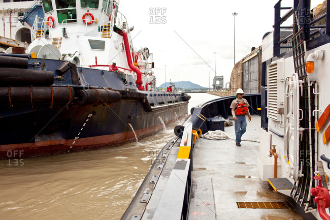Tugboats and workers in Panama Canal