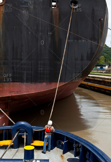 Cargo ship tied to tugboat