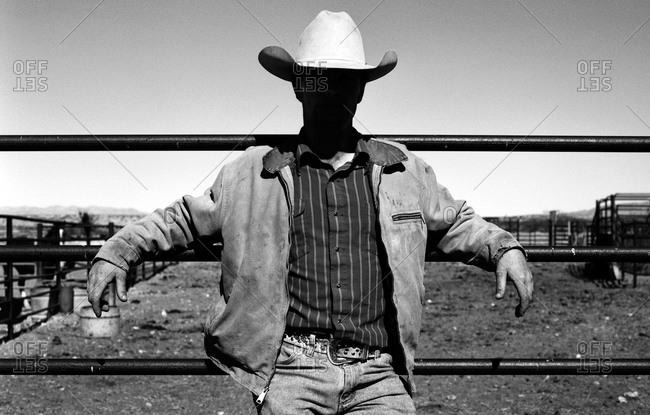 Cowboy resting on corral fence