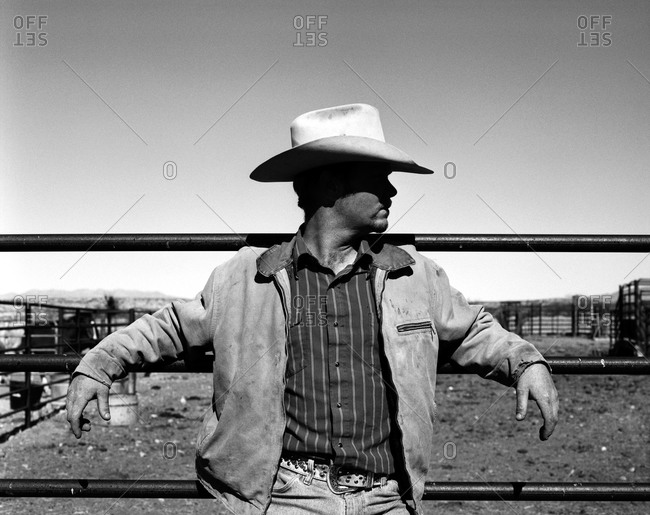 Cowboy leaning on corral fence
