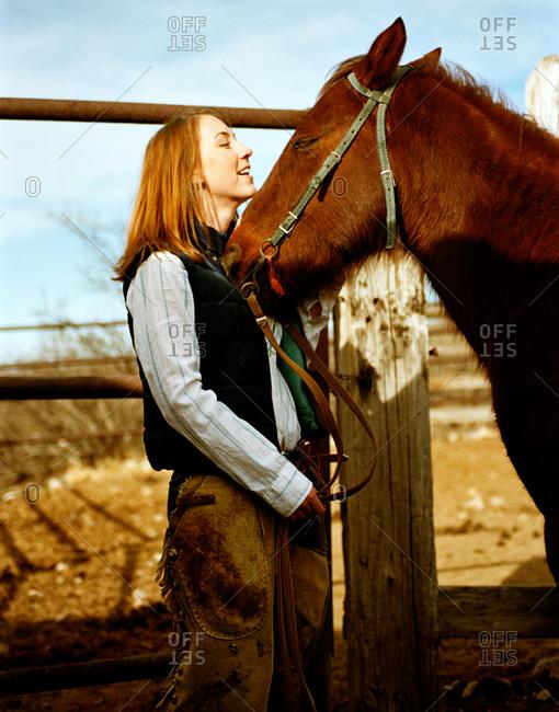 Cowgirl preparing her horse