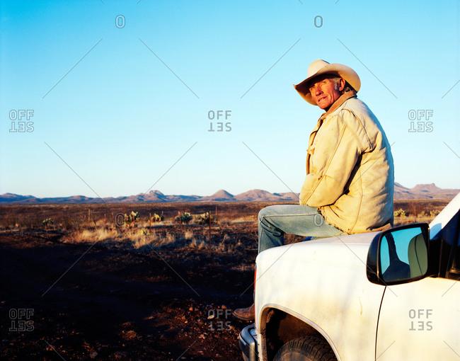 Cowboy on truck hood