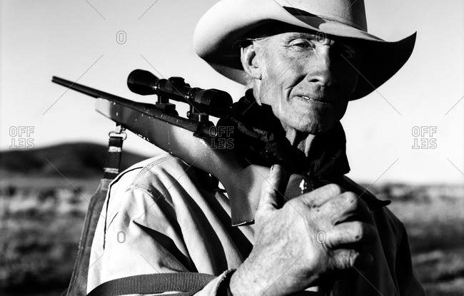 Cowboy carrying rifle on shoulder