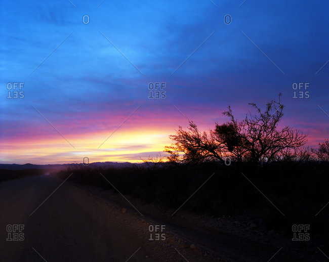 Sunset on dusty ranch road