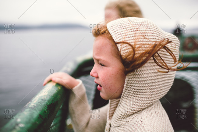Red-haired girl in hoodie on ferry boat