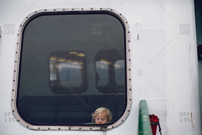 Little blonde boy looking out the window of a ferry boat