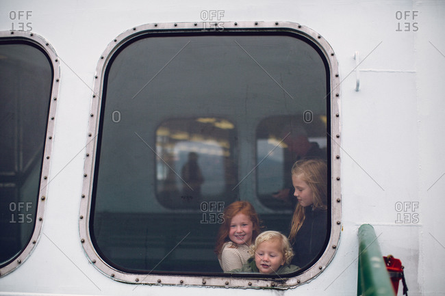 Three children seen through window of ferry boat