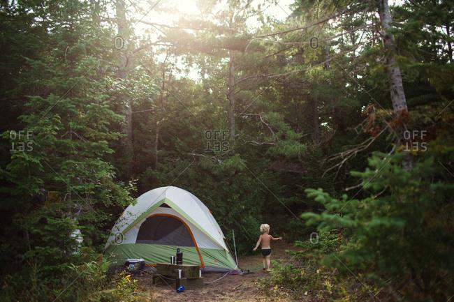 Little boy beside tent at campsite