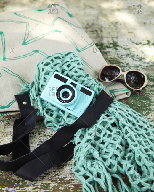 Analog camera and sunglasses on a tote bag
