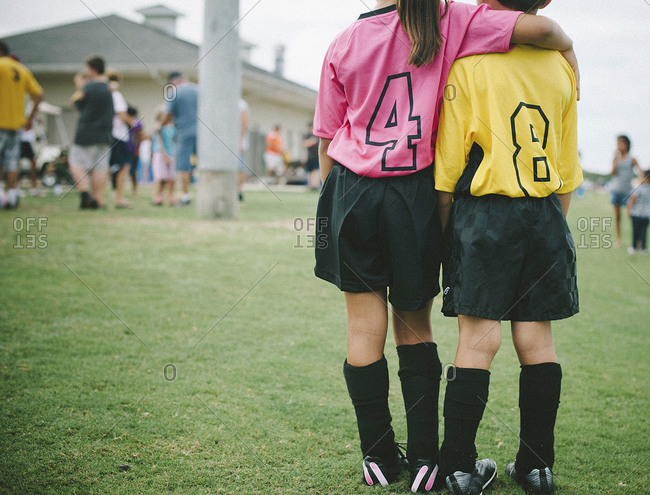 Two little children on different teams holding each other at soccer game