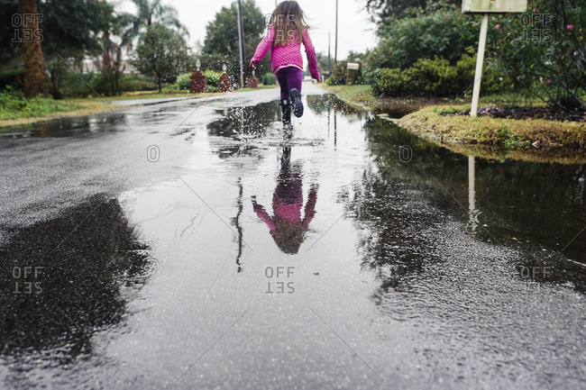 Little girl running through puddle during a rainstorm
