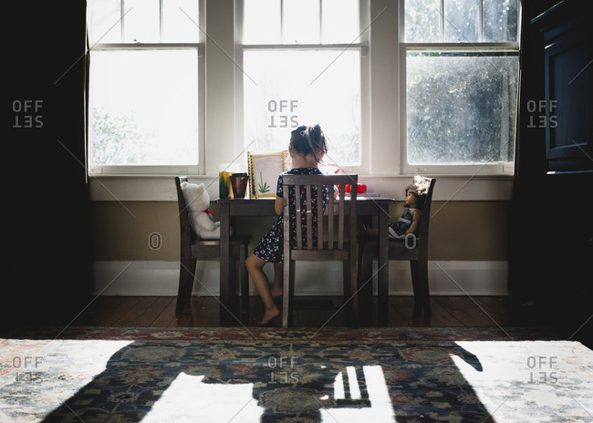Little girl at table by window with toys