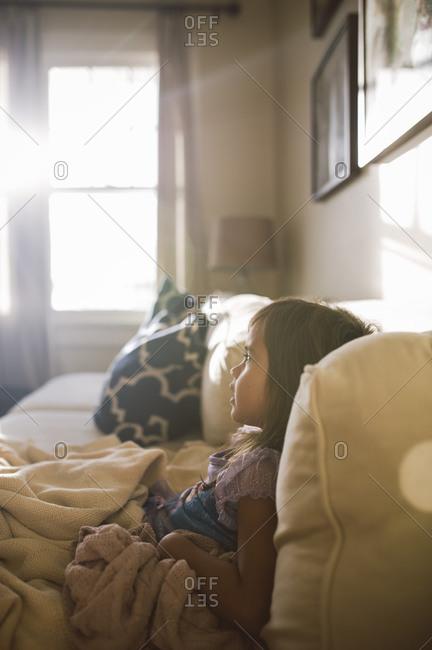 Little girl under blanket on couch