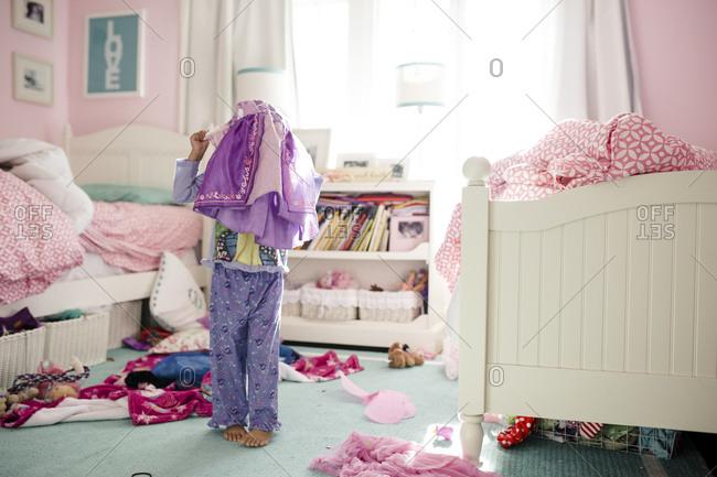 Little girl putting princess costume over pajamas