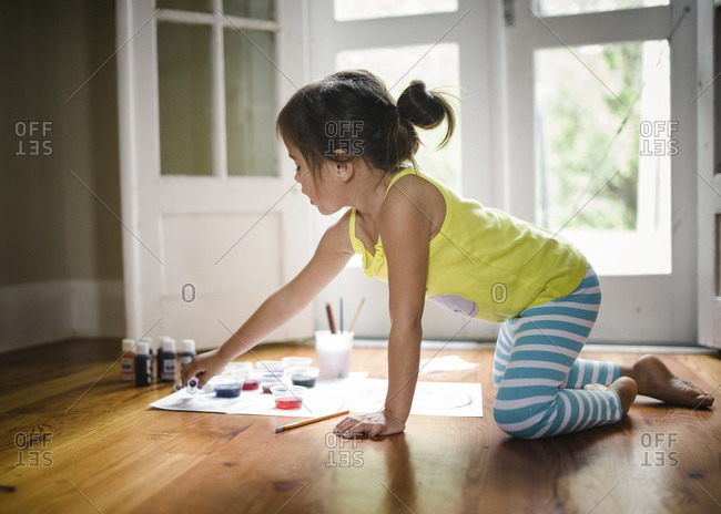 Little girl playing with paints on the floor
