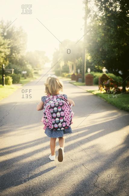 Little girl walking home from school by herself