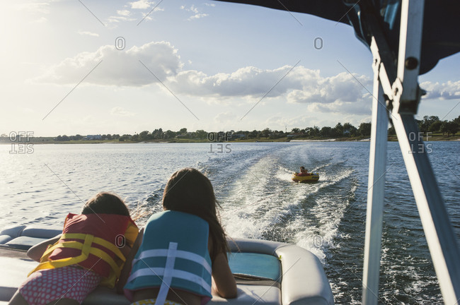 Two little girls on a motorboat watching a boy being pulled along in an inner tube