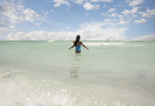 Girl wading in clear sea