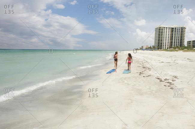 Little girls walking on white sand beach
