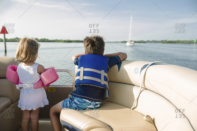 Boy and girl on boat watching other boat