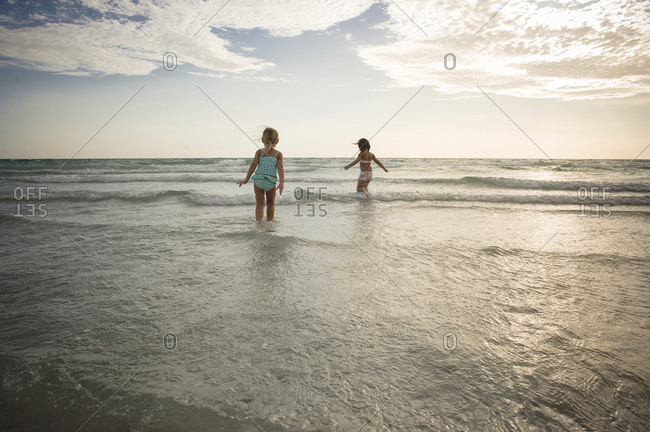 Little girls wading in a clear sea in the afternoon