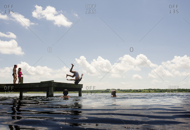 Girl jumping from dock into water