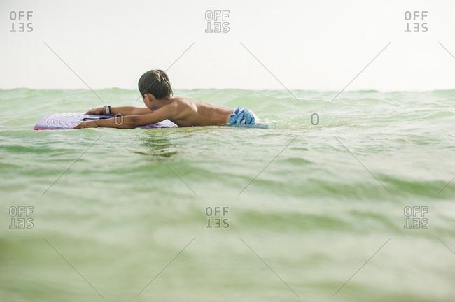 Boy floating on bodyboard in clear sea